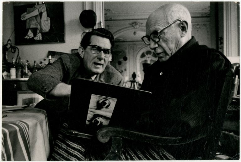 Photograph of Pablo Picasso looking at a Portfolio