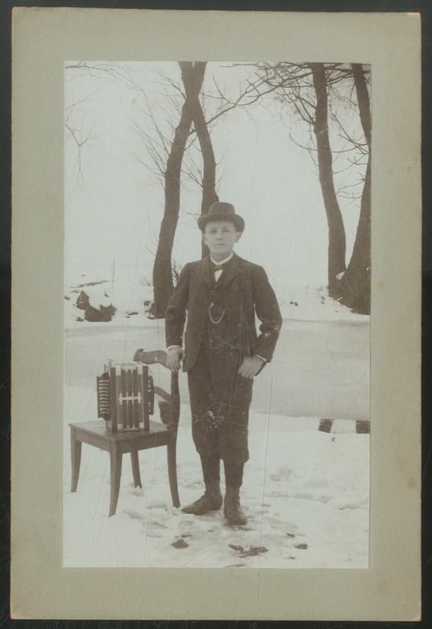 Cabinet Photograph of a Boy with an Accordion in the Snow
