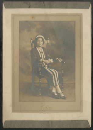Portrait photograph): African-American Seated in a High-back Chair holding a Flower (circa 1905